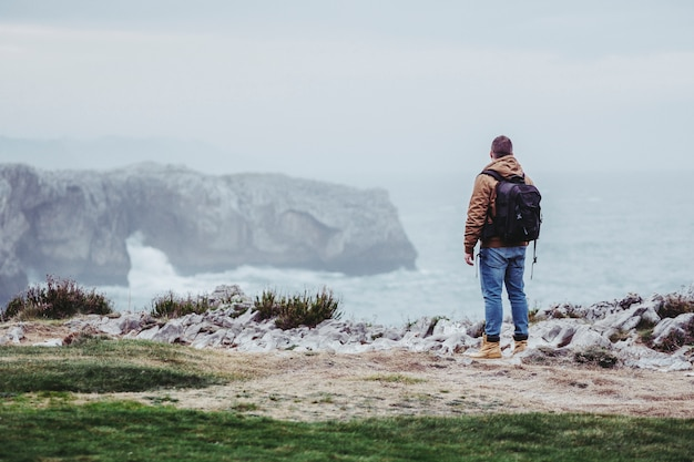 崖の上のバッグ観光を持つ男