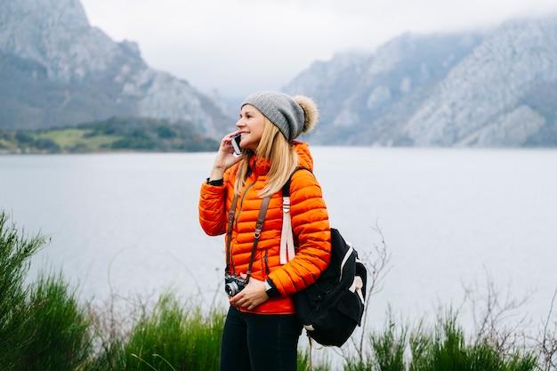 Красивая белокурая туристка в шерстяной шапке, рюкзаке и оранжевом пальто разговаривает по мобильному телефону на фоне пейзажа с озером и горами.