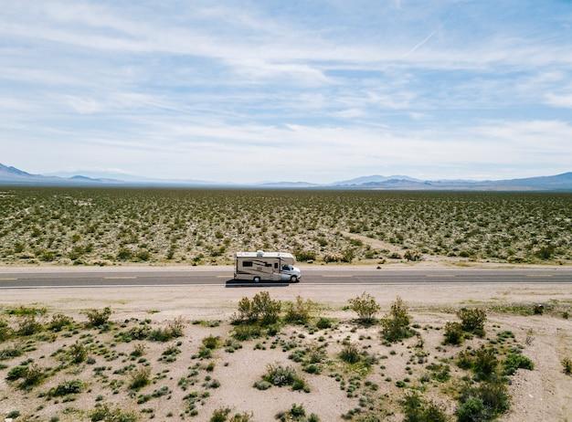 米国カリフォルニア州の砂漠の高速道路で運転するキャンピングカーの空撮