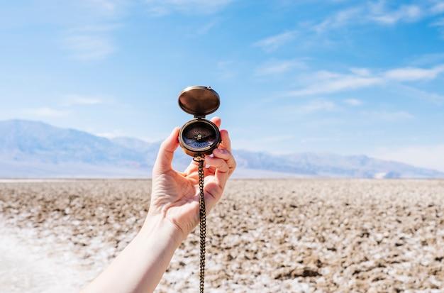 米国カリフォルニア州デスバレー砂漠の真ん中にコンパスを構える女性観光客。旅行中に晴れた日