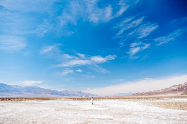 白と黄色の青の散歩で帽子と夏のドレスの美しい女性はジャンプを実行し、米国カリフォルニア州デスバレーの砂漠の風景を楽しんでいます