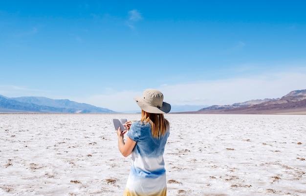 太陽の帽子と黄色と白の青い夏のドレスの美しいブロンドの女性は、晴れた日にデスバレーの砂漠で彼女の旅行ノートに描画して書き込みます