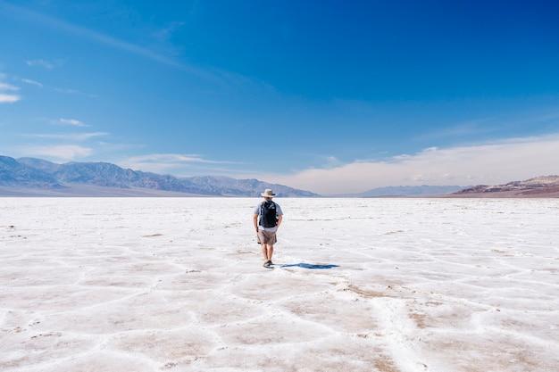 太陽から身を守る帽子と旅行者のバックパックを持った観光客の男性がデスバレー砂漠で晴れた日を楽しんでいます