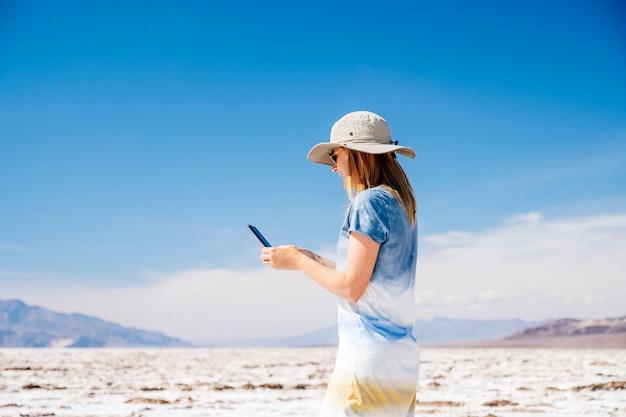 太陽の帽子と黄色と白の青い夏のドレスの美しいブロンドの女性は、晴れた日にデスバレーの砂漠で携帯電話を使用しています