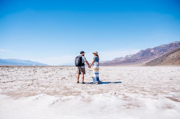キャップとバックパックを持つ男性と帽子と夏のドレスを持つ女性のカップルは、米国カリフォルニア州デスバレー砂漠で晴れた日を楽しみます