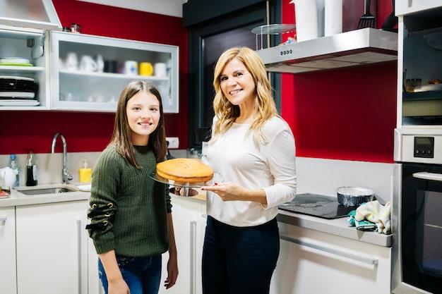 自宅の台所で娘と母親が家族で一緒にケーキを作る