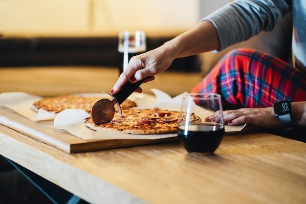 彼らのリビングルームのソファーでピザを食べるカップル