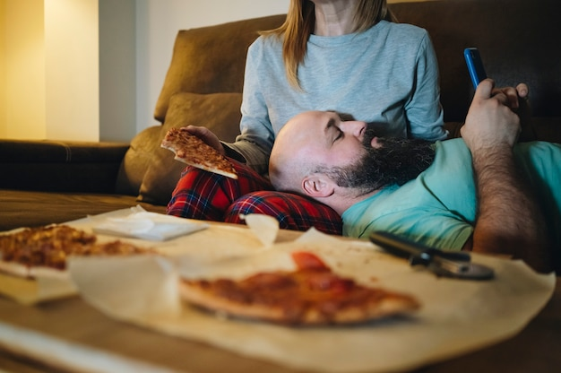 テレビで映画を見ながら、夜にリビングルームのソファーでピザを食べるカップル。