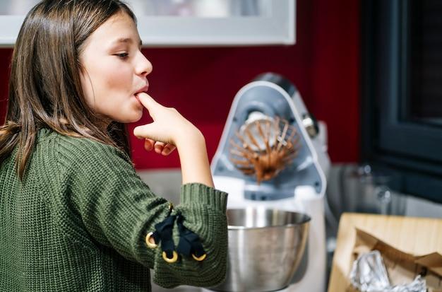 Женщина сосет свои смазанные шоколадом пальцы на своей домашней кухне