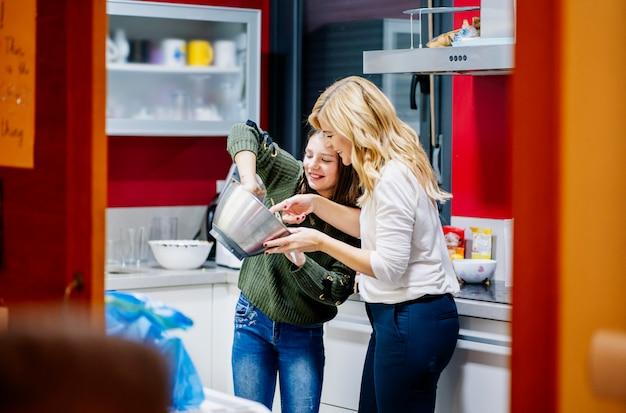 女性と娘が台所で一緒に料理する