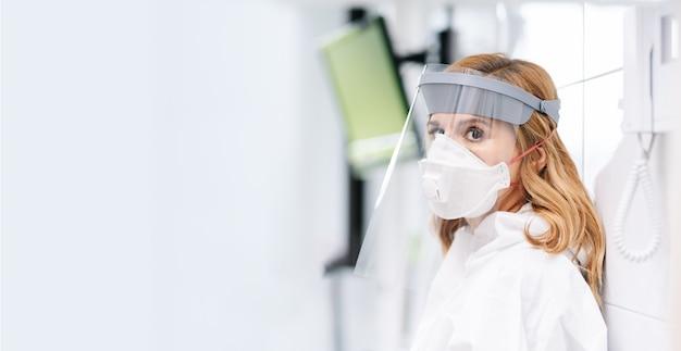 防護マスクを持つ女性医師の肖像画を閉じる