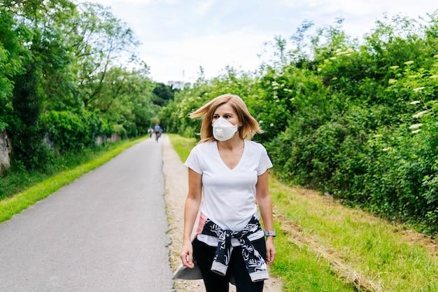 市内の公園を歩くフェイスマスクを持つ女性