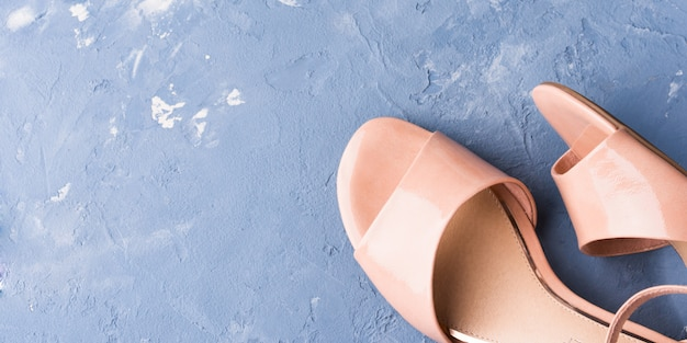 Пара женских розовых сандалий на синем