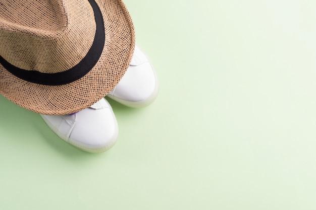 紫色のひもと麦わら帽子の白いスニーカー