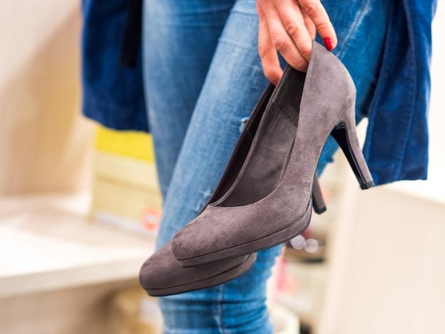 Женщина примеряет высокие каблуки в магазине
