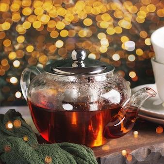 緑の背景の上のガラスのティーポットで熱いお茶