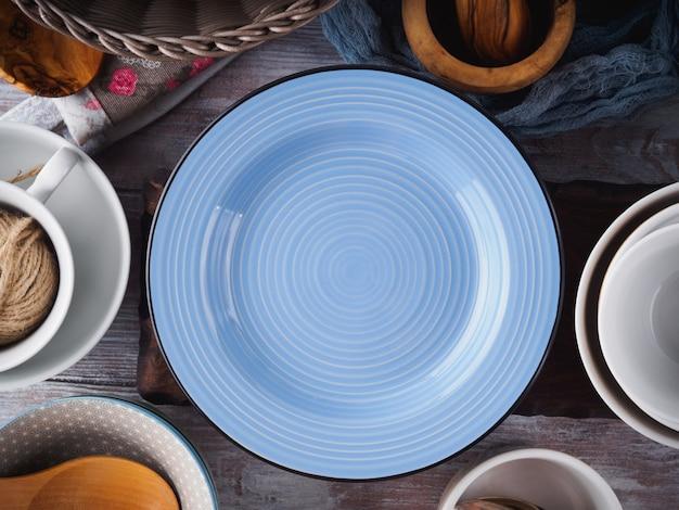 木製の背景にセラミックとエナメルの食器類食器。