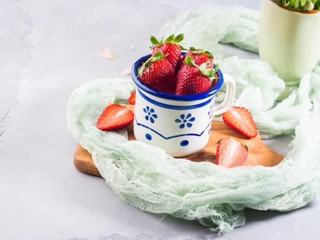 繊維と木の板にエナメルマグカップで熟したイチゴ。
