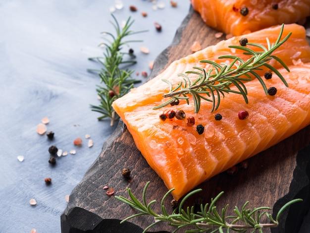 Сырой лосось на деревянной доске с травами