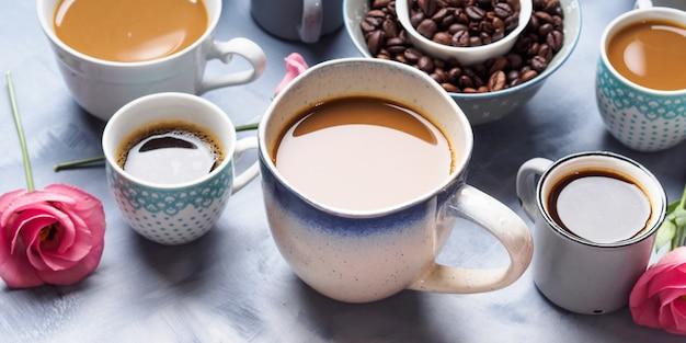 カップとコーヒーと青い背景上の花のマグカップ
