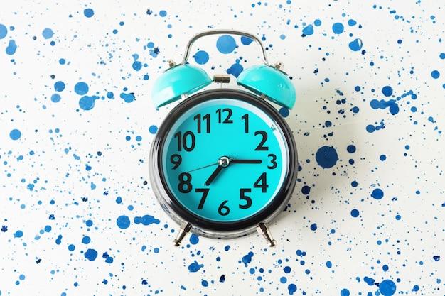 抽象的な背景に青い目覚まし時計。平置き