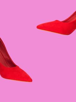 ピンクに分離された赤い女性ポンプ