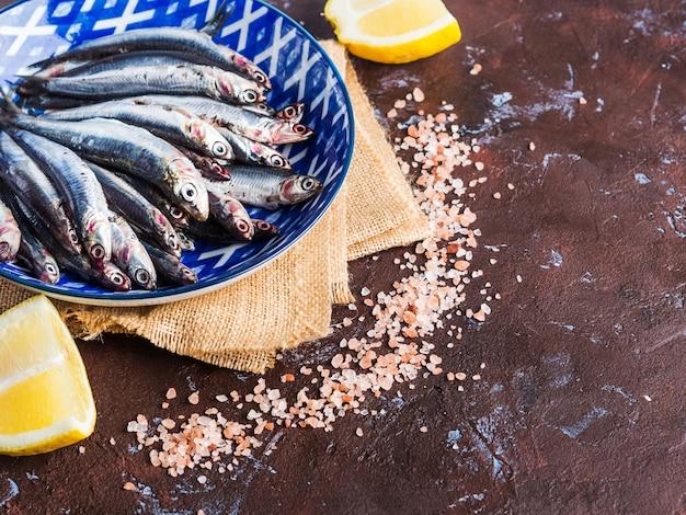 Синяя рыба. анчоусы в тарелке с розовой солью