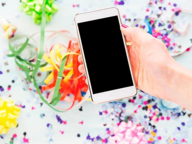 Мобильный телефон в руке над декором вечеринки