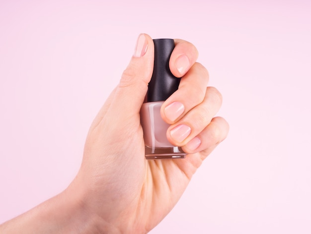 Женская рука держит обнаженный лак для ногтей