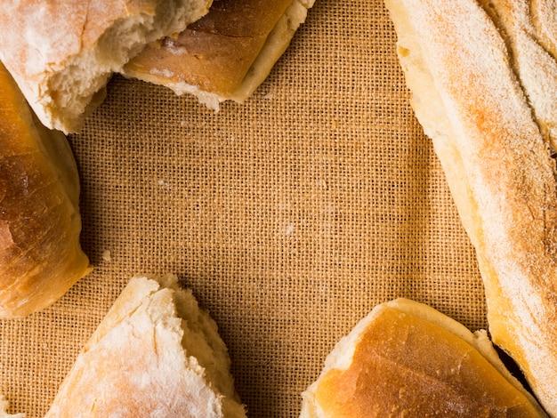 黄麻布の暗い木製の焼きたてのパン。テクスチャのクローズアップイタリアのベーカリー製品