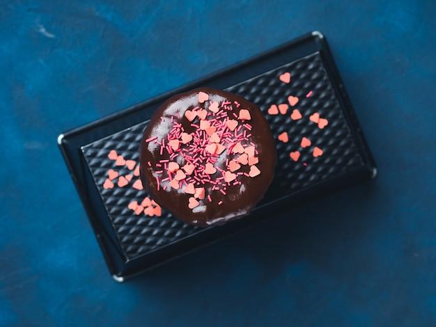 Бисквит из сливочного сыра с шоколадной глазурью и розовым сердцем посыпается темно-синим. день рождения валентина день матери угощение