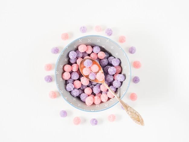 Фиолетовые и розовые конфеты в миске