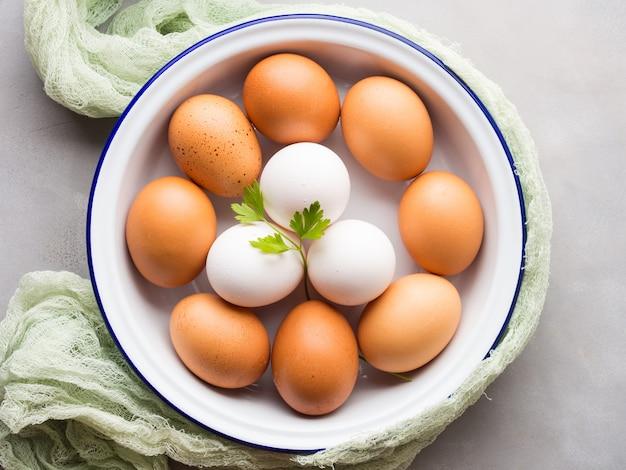 Белые и коричневые куриные яйца в миске