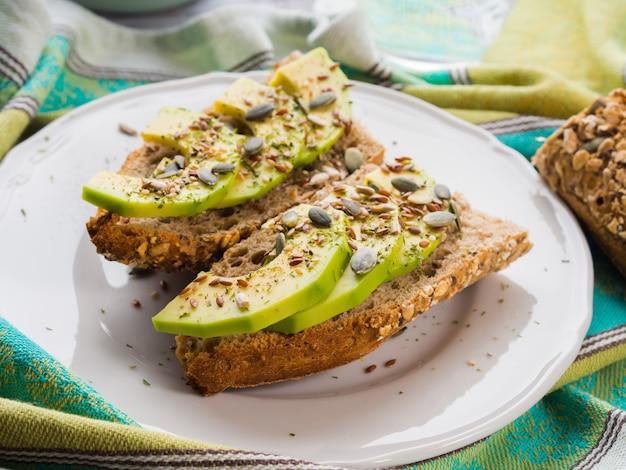 緑のナプキンに種と健康的なスナックのためのアボカドシリアルサンドイッチ