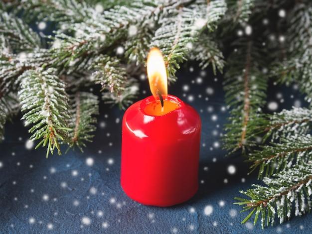Темный новогодний фон с красной свечой и снегом