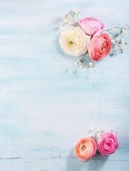 ターコイズブルーの木製の背景に美しいピンクキンポウゲフレーム。女性の母の日の結婚式。花の休日の優雅な束。