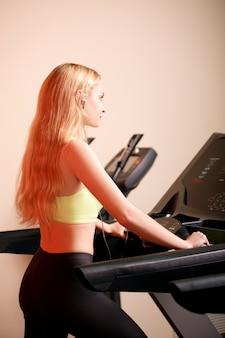Молодой спортсмен делает упражнения на беговой дорожке