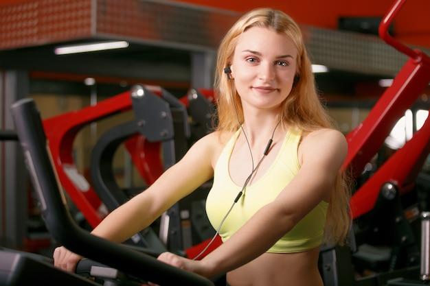 Тренировка молодой женщины на велосипеде в спортзале