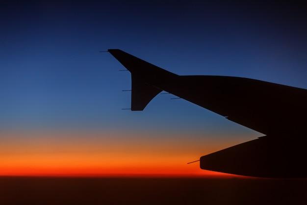 夕焼け空に対する航空機のシルエット