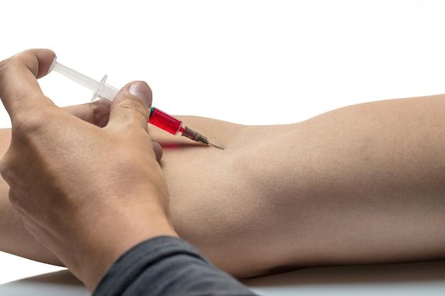 注射器で薬を注射する人