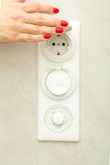 Женская рука поднимает защитную крышку на электрической розетке.