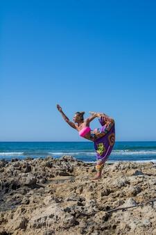 Красивая девушка со спортивной фигурой занимается йогой на свежем воздухе у моря. лето.