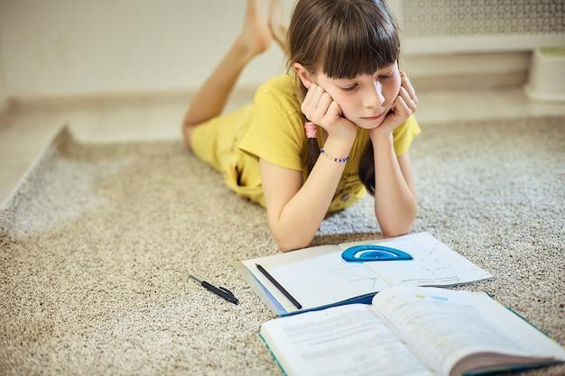 彼女の部屋のカーペットの上に座って宿題をしている十代の少女