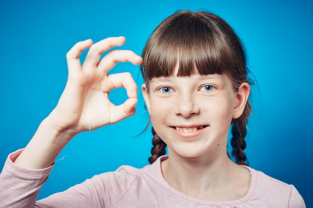 Ок, жест. улыбающаяся девушка-подросток. счастливое выражение лица