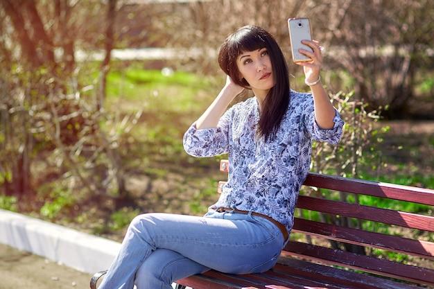 夏の公園で座っている美しい女の子