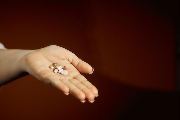 彼女の手に丸薬を保持している女性、風邪の治療。