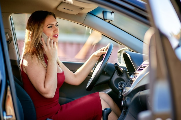赤いドレスのビジネスウーマンは車の中で座っていると電話で話しています。