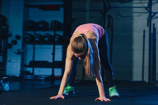 汚れた工業用スペースで紫色の運動マットの上のバーピーをやっているピンクのカラフルなスポーツウェアの女性に合う