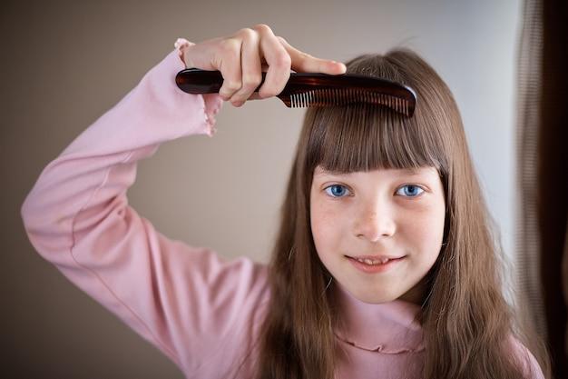 Маленькая девочка с веснушками и голубыми глазами расчесывает волосы