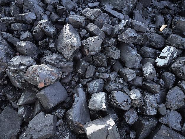 背景の天然黒石炭。工業用石炭